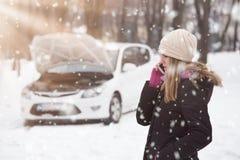 Mulher que usa o smartphone para chamar o auxílio da estrada inverno e vehic fotografia de stock royalty free