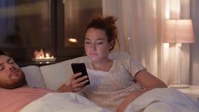 Mulher que usa o smartphone quando o noivo dormir video estoque