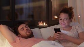Mulher que usa o smartphone quando o noivo dormir vídeos de arquivo