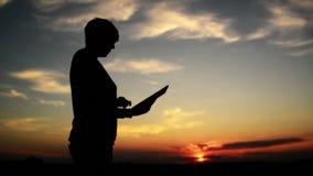 Mulher que usa o tablet pc digital para o Internet que consulta Silhueta fêmea com o dispositivo moderno que está no por do sol
