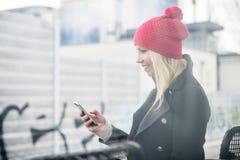 Mulher que usa o telefone ao esperar um trem suburbano fotografia de stock