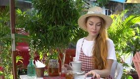 Mulher que usa o telefone celular ao beber o chá fora video estoque