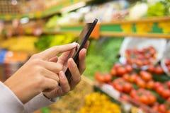 Mulher que usa o telefone celular ao comprar no supermercado
