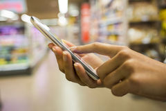 Mulher que usa o telefone celular ao comprar no supermercado Fotos de Stock Royalty Free