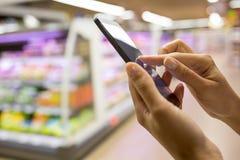 Mulher que usa o telefone celular ao comprar no supermercado Imagens de Stock Royalty Free