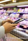 Mulher que usa o telefone celular ao comprar no supermercado Fotografia de Stock Royalty Free