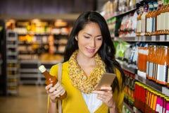 Mulher que usa o telefone celular ao comprar o mantimento Imagem de Stock