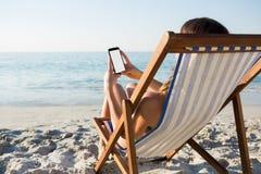 Mulher que usa o telefone celular ao relaxar na cadeira de sala de estar na praia imagens de stock royalty free