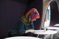 Mulher que usa o telefone celular durante meios do Social do tempo da ruptura do escritório fotografia de stock