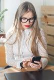 Mulher que usa o telefone celular e o portátil em casa imagem de stock royalty free