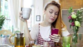 Mulher que usa o telefone celular e sorrindo ao beber o chá filme