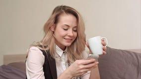 Mulher que usa o telefone celular na cama na noite e bebendo o chá Fotografia de Stock