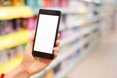 Mulher que usa o telefone celular na mercearia Foto de Stock