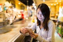 Mulher que usa o telefone celular no restaurante japonês fotos de stock