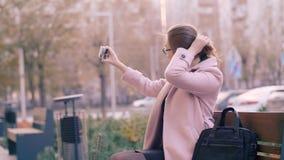 Mulher que usa o telefone celular para a foto do selfie na rede social no banco na cidade video estoque