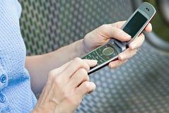 Mulher que usa o telefone de pilha fotografia de stock royalty free