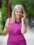 Mulher que usa o telefone de pilha na cidade imagens de stock