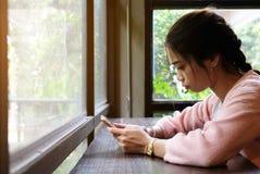 Mulher que usa o telefone esperto na tabela de madeira foto de stock royalty free