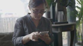 Mulher que usa o telefone esperto no restaurante filme