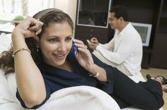 Mulher que usa o telemóvel no fim do sofá acima Fotografia de Stock