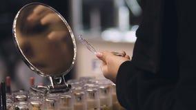 Mulher que usa o verificador da sombra para os olhos, escolhendo a cor e a qualidade dos cosméticos, composição filme