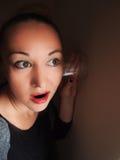 Mulher que usa o vidro de encontro à parede para eavesdrop imagens de stock
