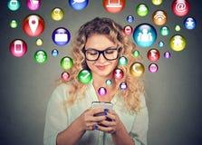 Mulher que usa os ícones sociais da aplicação dos meios do smartphone que voam fora da tela Fotos de Stock