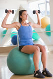 Mulher que usa pesos da mão na esfera suíça na ginástica Fotos de Stock Royalty Free