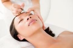 Mulher que usa a pinça na sobrancelha paciente Fotos de Stock Royalty Free