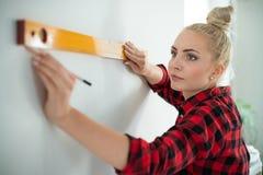 Mulher que usa-se nivelando a ferramenta em casa imagem de stock royalty free