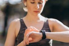 Mulher que usa seu dispositivo wearable da tecnologia do écran sensível do smartwatch em luzes da manhã fotos de stock royalty free