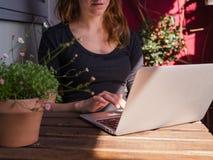 Mulher que usa seu portátil fora no balcão Fotos de Stock