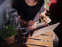 Mulher que usa seu portátil fora no balcão Fotografia de Stock Royalty Free