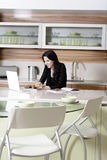 Mulher que usa seu portátil na cozinha Fotos de Stock Royalty Free