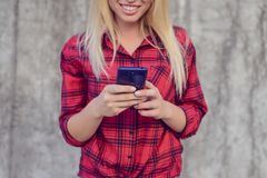 Mulher que usa seu smartphone para surfar o Internet, é watc imagem de stock