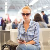 Mulher que usa seu telefone celular ao esperar para embarcar um plano em portas de partida no aeroporto internacional foto de stock royalty free