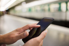 Mulher que usa seu telefone celular na plataforma do metro Fotos de Stock Royalty Free