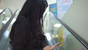 Mulher que usa seu telefone celular no mal na escada rolante video estoque