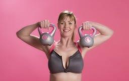 Mulher que usa sinos da chaleira para exercitar Fotos de Stock Royalty Free