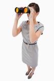 Mulher que usa spyglasses Imagem de Stock Royalty Free