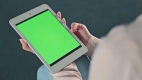 Mulher que usa a tabuleta com tela verde vídeos de arquivo