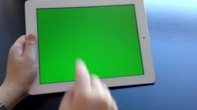 Mulher que usa a tabuleta digital com uma tela verde