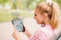 Mulher que usa a tabuleta digital no parque imagem de stock