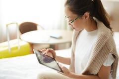 Mulher que usa a tabuleta digital no quarto fotografia de stock royalty free