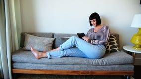 Mulher que usa a tabuleta digital no sofá em casa vídeos de arquivo