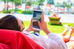 Mulher que usa a tabuleta em férias de verão Foto de Stock Royalty Free
