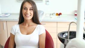 Mulher que usa a tabuleta na sala dental e sorrindo na câmera video estoque