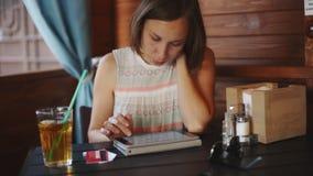 Mulher que usa a tabuleta no café vídeos de arquivo