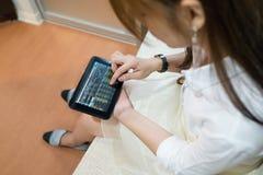 Mulher que usa a tabuleta para verificar o mercado de valores de ação imagens de stock