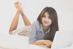 Mulher que usa um laptop ao encontrar-se em sua cama Fotografia de Stock